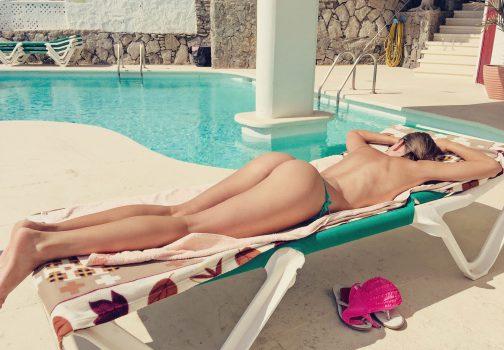 Femme mature allongée sur un transat de piscine