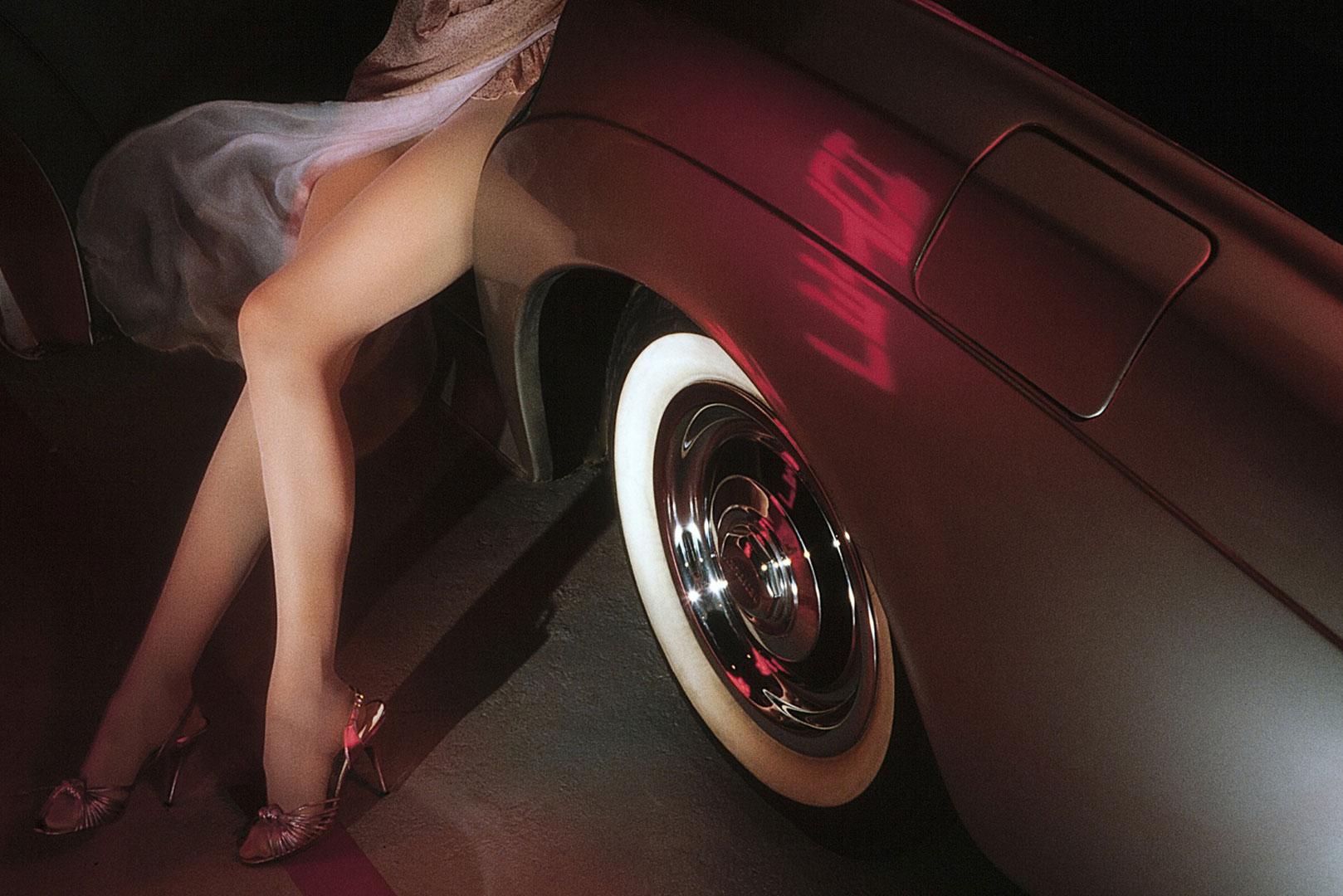 Une jolie paire de jambes de femme près d'une voiture américaine